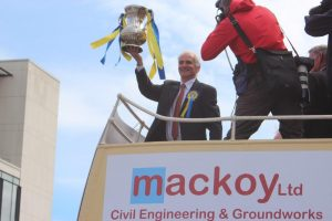 Holding the FA Cup on top of the bus